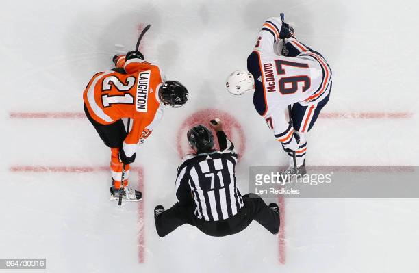 Linesman Brad Kovachik prepares to drop the puck for a faceoff between Scott Laughton of the Philadelphia Flyers and Connor McDavid of the Edmonton...