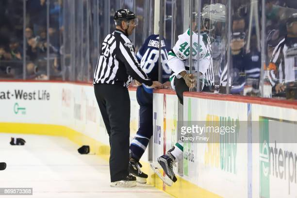 Linesman Brian Mach ensures that Brendan Lemieux of the Winnipeg Jets and Gemel Smith of the Dallas Stars head into the penalty box after a first...
