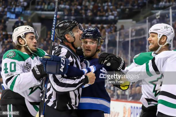 Linesman Brian Mach has words with Marc Methot of the Dallas Stars as he separates Brendan Lemieux of the Winnipeg Jets from the scrum during second...