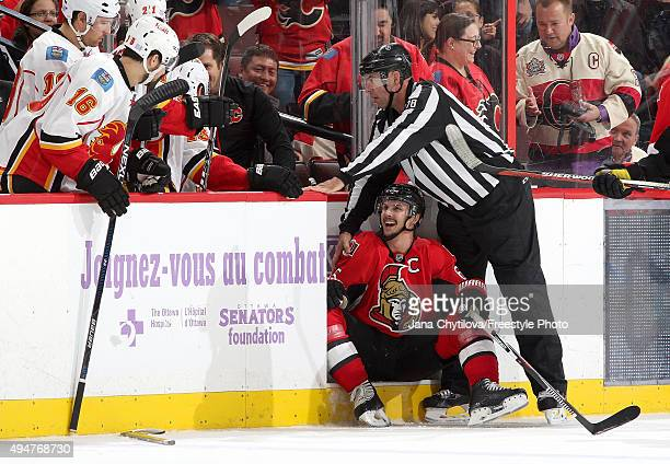Linesman Brian Mach helps Erik Karlsson of the Ottawa Senators after he got caught up in the skate of Johnny Gaudreau of the Calgary Flames and could...