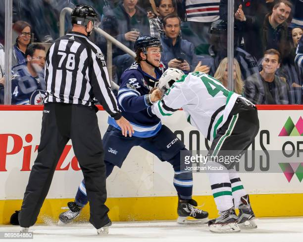 Linesman Brian Mach keeps an eye on a first period fight between Brendan Lemieux of the Winnipeg Jets and Gemel Smith of the Dallas Stars at the Bell...