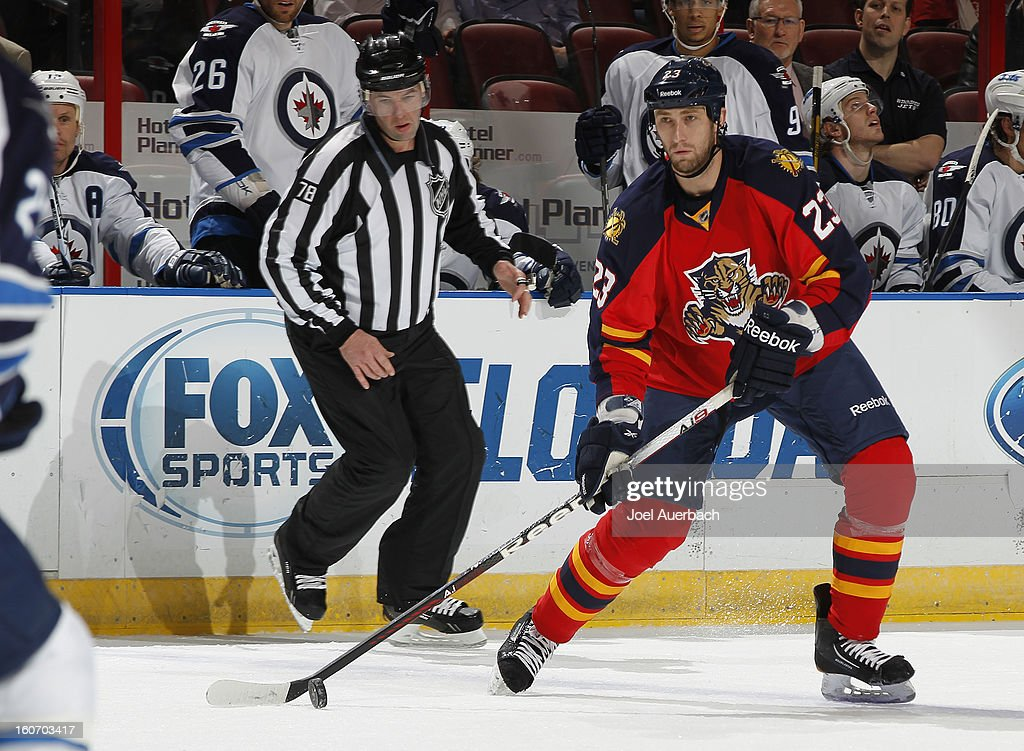 Linesman Brian Mach #78 looks on as Tyson Strachan #23 of the Florida Panthers prepares to shoot the luck towards the Winnipeg Jets net at the BB&T Center on January 31, 2013 in Sunrise, Florida. The Panthers defeated the Jets 6-3.