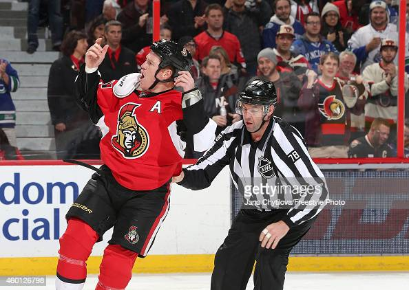 Linesman Brian Mach steers Chris Neil of the Ottawa Senators to the penalty box as he tries to get the fans going following a fight in the second...