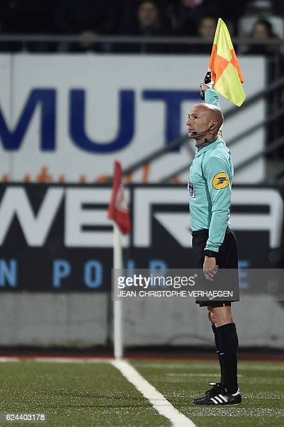 Linesman Cyril SaintCricq Lompre raises the flag for offside during the French L1 football match between Nancy and Dijon at the Marcel Picot stadium...