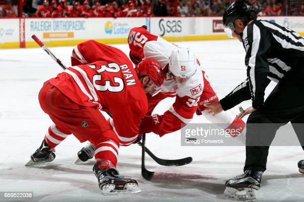 Linesman Darren Gibbs drops the puck for a faceoff between Derek Ryan of the Carolina Hurricanes and Frans Nielsen of the Detroit Red Wings during an...