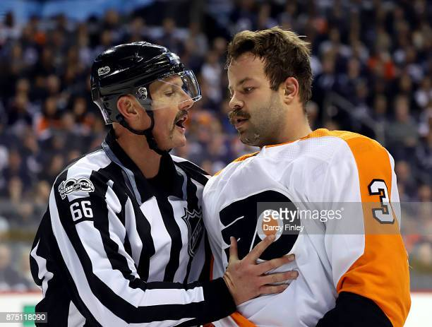 Linesman Darren Gibbs gets a hold of Radko Gudas of the Philadelphia Flyers after a first period altercation against the Winnipeg Jets at the Bell...