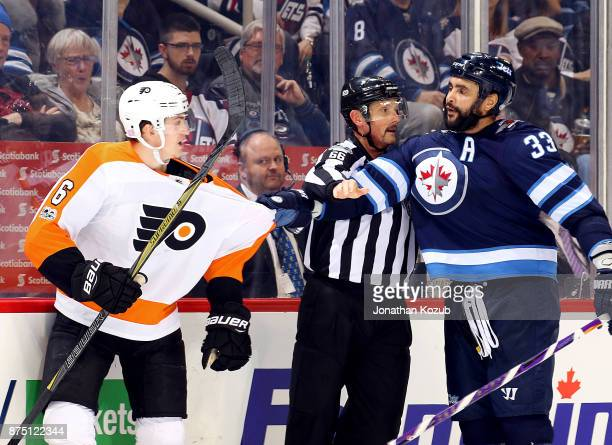 Linesman Darren Gibbs gets between Dustin Byfuglien of the Winnipeg Jets and Travis Sanheim of the Philadelphia Flyers before a scrum can break out...