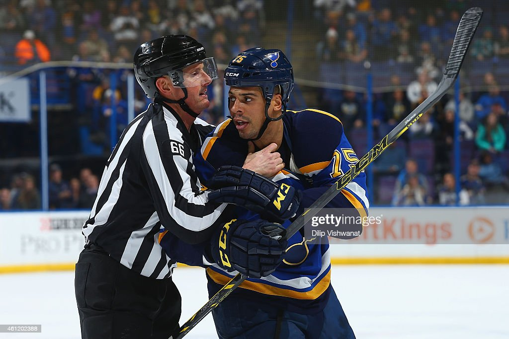 Linesman Darren Gibbs restrains Ryan Reaves of the St Louis Blues during a game against the San Jose Sharks at the Scottrade Center on January 8 2015...