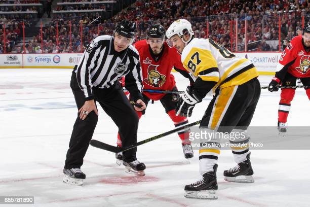 Linesman Derek Amell checks the positions of players prior to a faceoff between JeanGabriel Pageau the Ottawa Senators and Sidney Crosby of the...