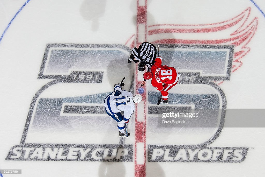 Linesman Derek Amell drops the puck between Joakim Andersson of the Detroit Red Wings and Brian Boyle of the Tampa Bay Lightning during Game Three of...