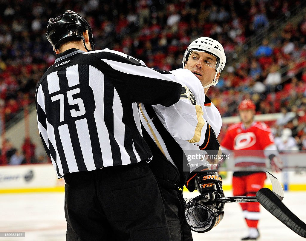 Linesman Derek Amell #75 helps Francois Beauchemin #23 of the Anaheim Ducks with his equipment during a game against the Carolina Hurricanes at the RBC Center on February 23, 2012 in Raleigh, North Carolina.