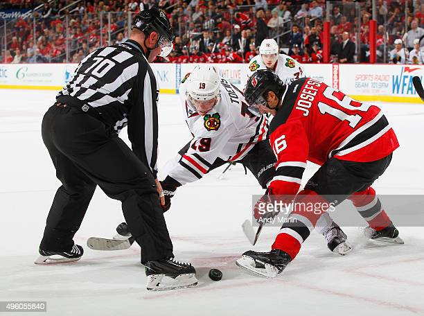 Linesman Derek Nansen drops the puck on a faceoff between Jacob Josefson of the New Jersey Devils and Jonathan Toews of the Chicago Blackhawks during...