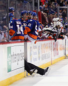 Linesman Derek Nansen falls through the empty bench door during the game between the New York Islanders and the Anaheim Ducks at the Barclays Center...