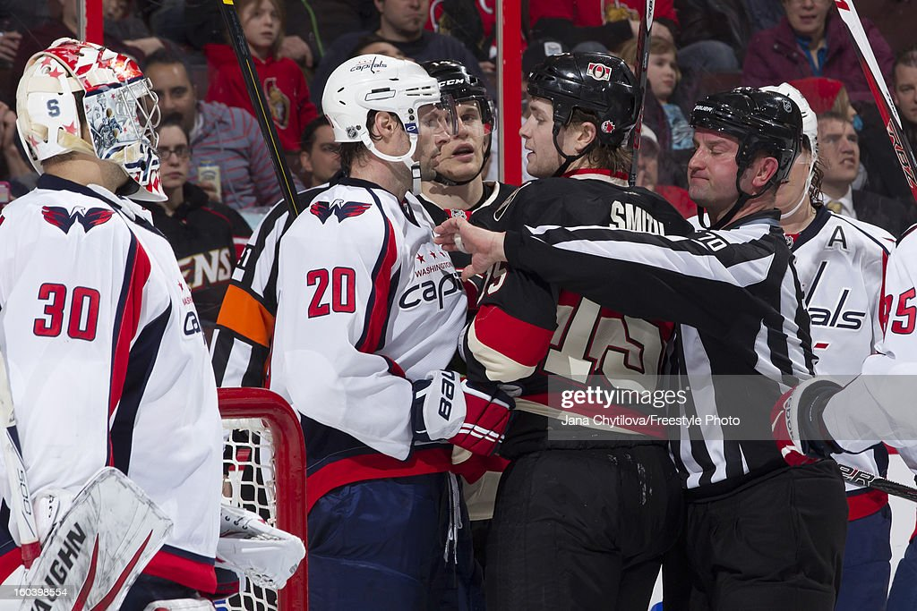 Linesman Derek Nansen #70 tries to separate Zack Smith #15 of the Ottawa Senators and Troy Brouwer #20 of the Washington Capitals during an NHL game at Scotiabank Place on January 29, 2013 in Ottawa, Ontario, Canada.