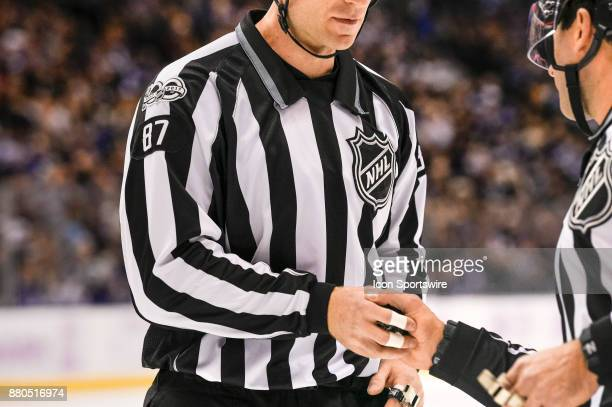 Linesman Devin Berg gets handed the puck by another official during the NHL regular season hockey game between the Washington Capitals and Toronto...