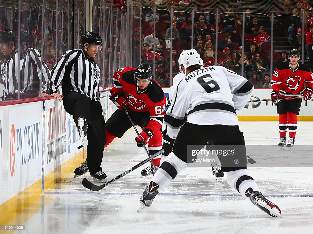 Linesman Devin Berg #87 is tripped up by Joseph Blandisi #64 of the New Jersey Devils as he eyes the puck while being defended by <a gi-track='captionPersonalityLinkClicked' href=/galleries/search?phrase=Jake+Muzzin&family=editorial&specificpeople=7205557 ng-click='$event.stopPropagation()'>Jake Muzzin</a> #6 of the Los Angeles Kings during the game at the Prudential Center on February 14, 2016 in Newark, New Jersey.