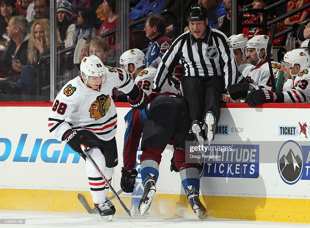 Linesman Don Henderson #91 avoids the action as Patrick Kane #88 of the Chicago Blackhawks puts a hit on Marc-Andre Cliche #24 of the Colorado Avalanche at Pepsi Center on March 12, 2014 in Denver, Colorado.