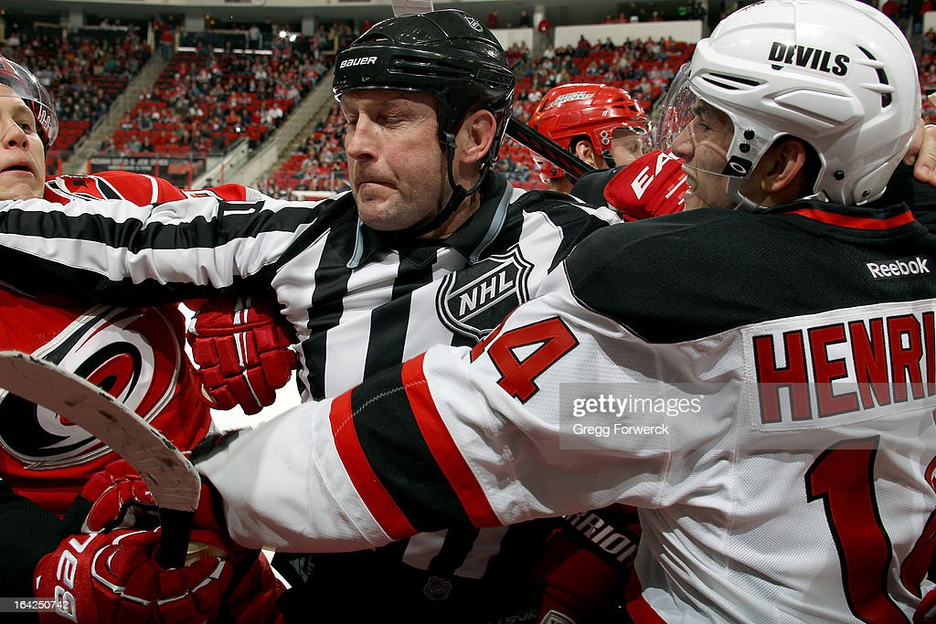 Linesman Don Henderson separates Jeff Skinner of the Carolina Hurricanes and Adam Henrique #14 of the New Jersey Devils during a skirmish late in the third period of their NHL game at PNC Arena on March 21, 2013 in Raleigh, North Carolina.