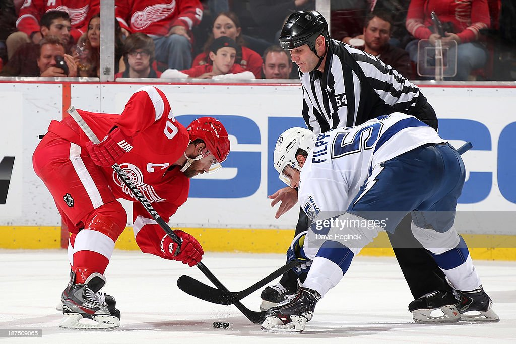 Linesman Greg Devorski #54 drops the puck as <a gi-track='captionPersonalityLinkClicked' href=/galleries/search?phrase=Henrik+Zetterberg&family=editorial&specificpeople=201520 ng-click='$event.stopPropagation()'>Henrik Zetterberg</a> #40 of the Detroit Red Wings and <a gi-track='captionPersonalityLinkClicked' href=/galleries/search?phrase=Valtteri+Filppula&family=editorial&specificpeople=2234404 ng-click='$event.stopPropagation()'>Valtteri Filppula</a> #51 of the Tampa Bay Lightning face-off during an NHL game at Joe Louis Arena on November 9, 2013 in Detroit, Michigan. Tampa Bay defeated Detroit 3-2 in OT