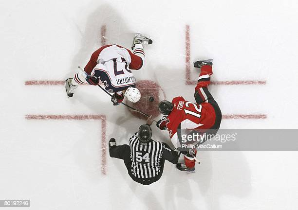 Linesman Greg Devorski drops the puck on a face off between Manny Malhotra of the Columbus Blue Jackets and Mike Fisher of the Ottawa Senators during...