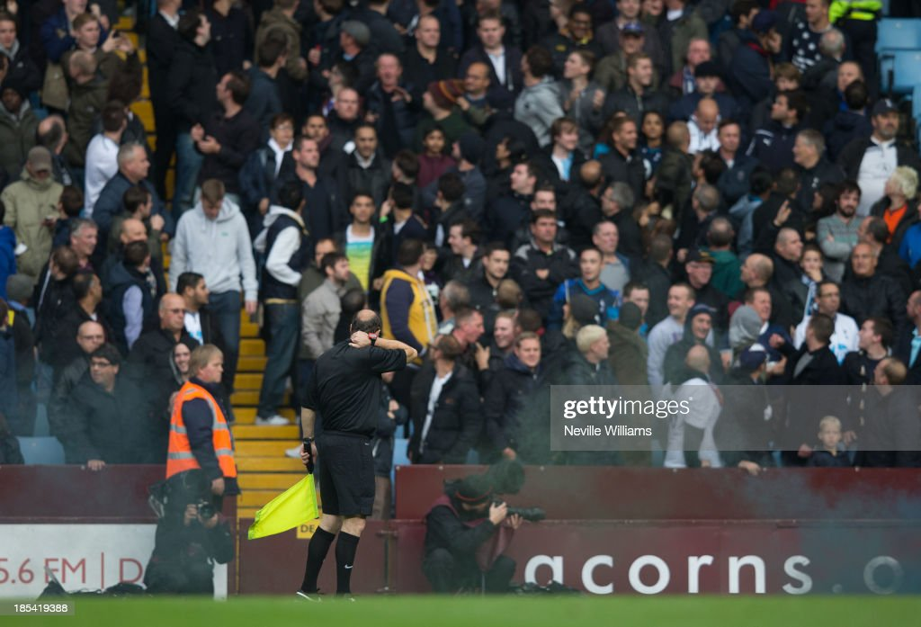 A linesman is hit by a flare during the Barclays Premier League match between Aston Villa and Tottenham Hotspur at Villa Park on October 20, 2013 in Birmingham, England.