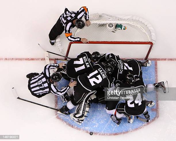 NHL linesman Jean Morin and referee Dan O'Rourke watch as Jordan Nolan Simon Gagne Colin Fraser and Rob Scuderi of the Los Angeles Kings pile on top...
