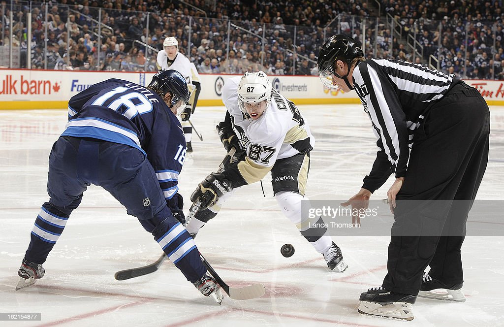 Linesman Jean Morin #97 drops the puck between Bryan Little #18 of the Winnipeg Jets and Sidney Crosby #87 of the Pittsburgh Penguins during a third period face-off at the MTS Centre on February 15, 2013 in Winnipeg, Manitoba, Canada. The Penguins defeated the Jets 3-1.