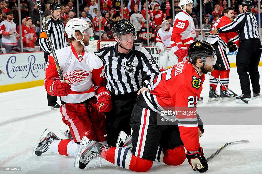 Linesman Jean Morin #97 separates Jakub Kindl #4 of the Detroit Red Wings and Viktor Stalberg #25 of the Chicago Blackhawks, while in the background Andrew Shaw #65 of the Blackhawks is pulled away from Carlo Colaiacovo #28 of the Red Wings by linesman Jonny Murray #95, in Game Five of the Western Conference Semifinals during the 2013 Stanley Cup Playoffs at the United Center on May 25, 2013 in Chicago, Illinois.