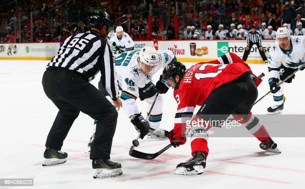 Linesman Jonny Murray drops the puck on a faceoff between Nico Hischier of the New Jersey Devils and Ryan Carpenter of the San Jose Sharks during the...