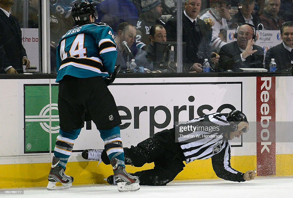 Linesman Jonny Murray #95 goes down to the ice after getting hit with the puck off the stick of Marc-Edouard Vlasic #44 of the San Jose Sharks during a NHL game against the Chicago Blackhawks at HP Pavilion on February 5, 2013 in San Jose, California.