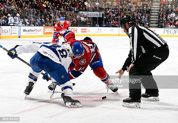 Linesman Kevin Ferguson drops the puck between Mark Arobello of the Toronto Marlies and Charles Hudon of the St Johns IceCaps during AHL game action...