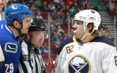 Linesman Kiel Murchison gets between Tom Sestito of the Vancouver Canucks and Marcus Foligno of the Buffalo Sabres as they talk to each other at the...