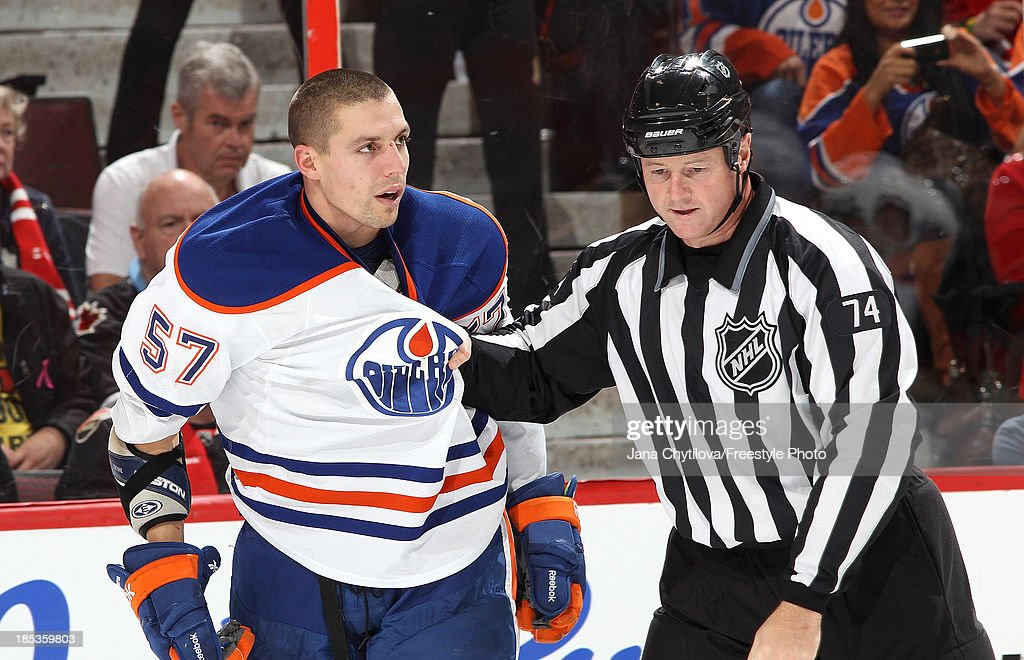 Linesman Lonnie Cameron #74 holds onto the jersey of <a gi-track='captionPersonalityLinkClicked' href=/galleries/search?phrase=David+Perron&family=editorial&specificpeople=4282591 ng-click='$event.stopPropagation()'>David Perron</a> #57 of the Edmonton Oilers after a scrum during an NHL game at Canadian Tire Centre on October 19, 2013 in Ottawa, Ontario, Canada.