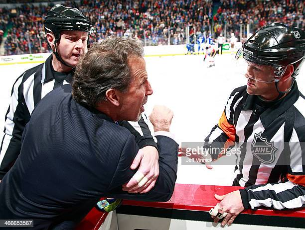 Linesman Lonnie Cameron looks on referee Kyle Rehman talks to head coach John Tortorella of the Vancouver Canucks who is shouting at the Calgary...