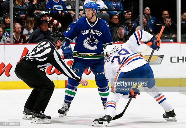 Linesman Lonnie Cameron prepares to drop the puck between Nick Bonino of the Vancouver Canucks and Leon Draisaitl of the Edmonton Oilers during their...