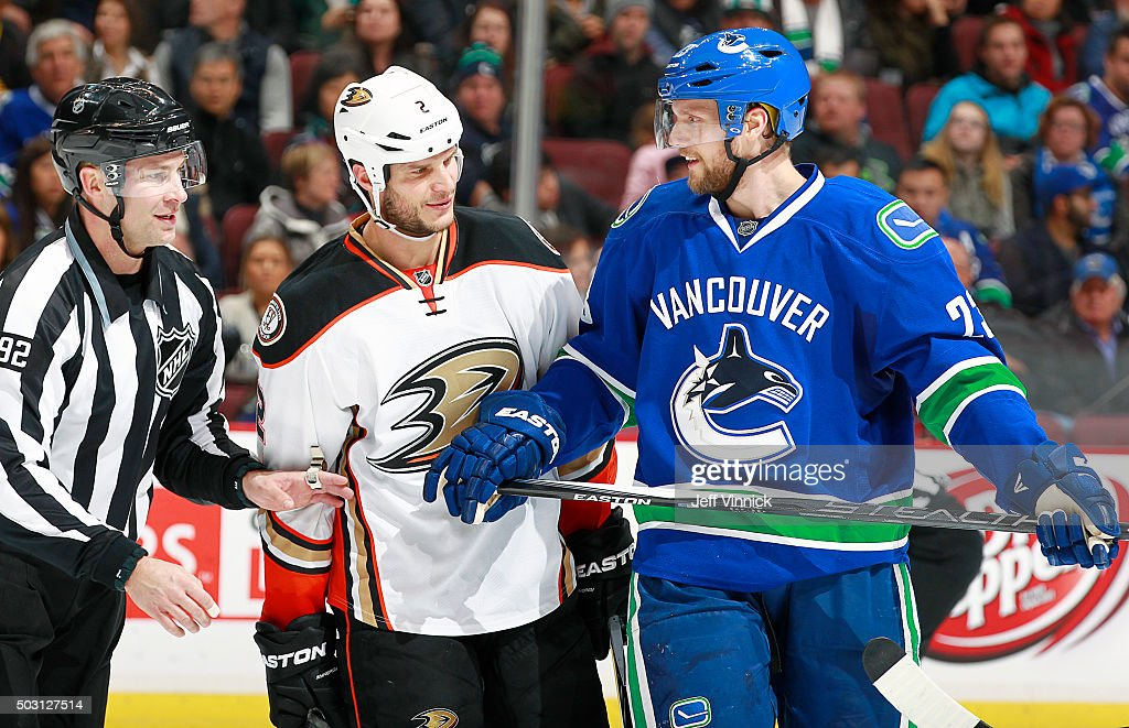 Linesman Mark Shewchyk separates former teammates Kevin Bieksa #2 of the Anaheim Ducks and Alexander Edler #23 of the Vancouver Canucks during their NHL game at Rogers Arena January 1, 2016 in Vancouver, British Columbia, Canada.