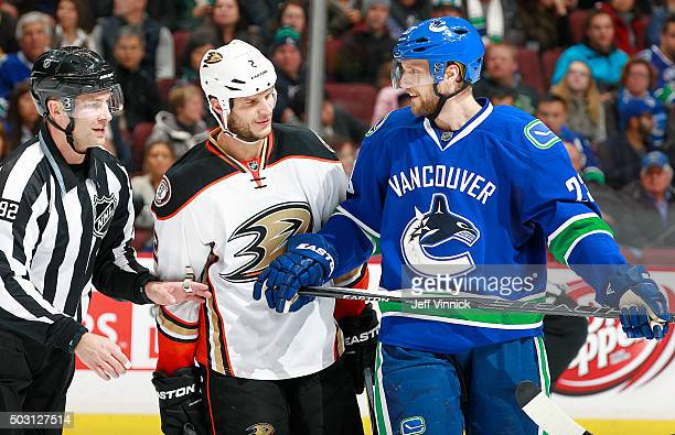 Linesman Mark Shewchyk separates former teammates Kevin Bieksa of the Anaheim Ducks and Alexander Edler of the Vancouver Canucks during their NHL...