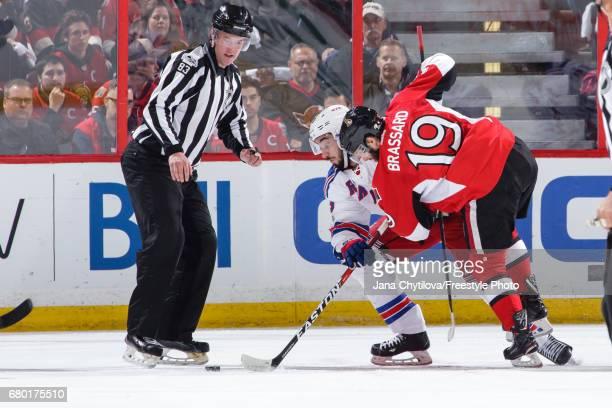 Linesman Matt MacPherson looks on as Derick Brassard of the Ottawa Senators takes a faceoff against Mika Zibanejad of the New York Rangers in Game...