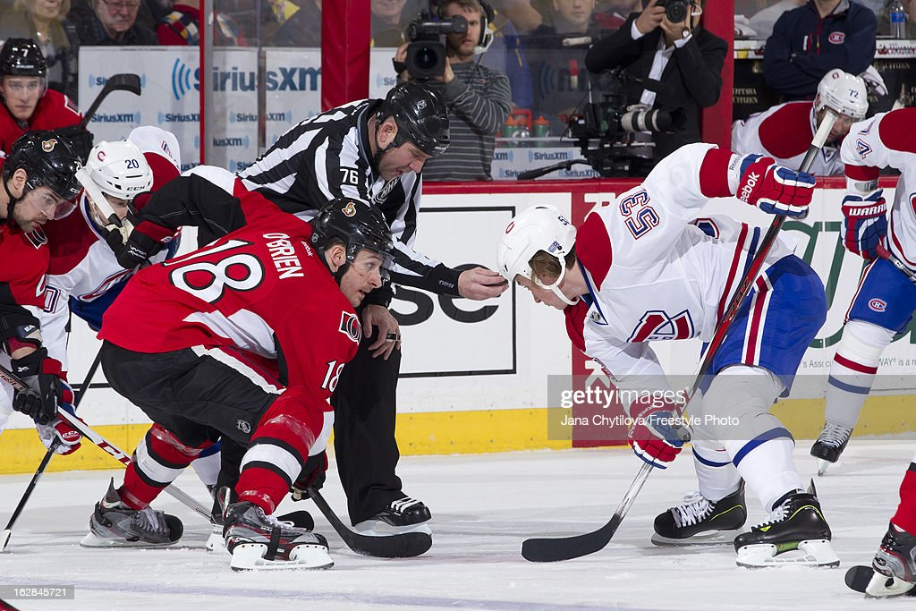 Linesman Michel Cormier #76 holds the puck as Jim O'Brien #18 of the Ottawa Senators takes a faceoff against Ryan White #53 of the Montreal Canadiens, during an NHL game, at Scotiabank Place on February 25, 2013 in Ottawa, Ontario, Canada.