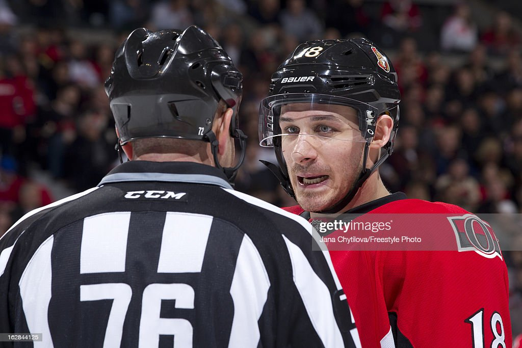 Linesman Michel Cormier #76 talks with Jim O'Brien #18 of the Ottawa Senators, during an NHL game against the Montreal Canadiens, at Scotiabank Place on February 25, 2013 in Ottawa, Ontario, Canada.