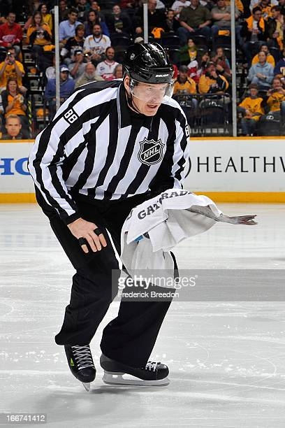 Linesman Mike Cvik picks up a catfish during a game between the Nashville Predators and the Detroit Red Wings at the Bridgestone Arena on April 14...