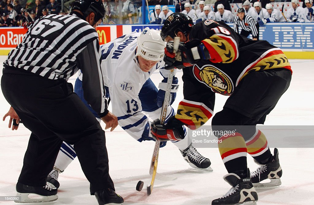Linesman Pierre Champoux #67 drops the puck as center Mats Sundin #13 of the Toronto Maple Leafs faces off against Jody Hull #16 of the Ottawa Senators during the game on October 12, 2002 at Air Canada Centre in Toronto, Ontario, Canada.