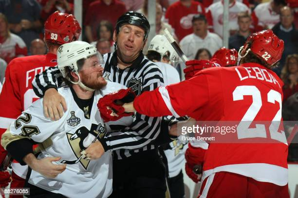 Linesman Pierre Racicot breaks up a scuffle between Matt Cooke of the Pittsburgh Penguins and Brett Lebda of the Detroit Red Wings during Game Five...