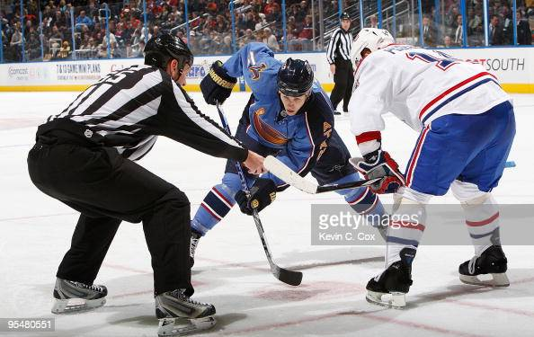 Linesman Pierre Racicot drops the puck for a face off between Tomas Plekanec of the Montreal Canadiens and Marty Reasoner of the Atlanta Thrashers at...