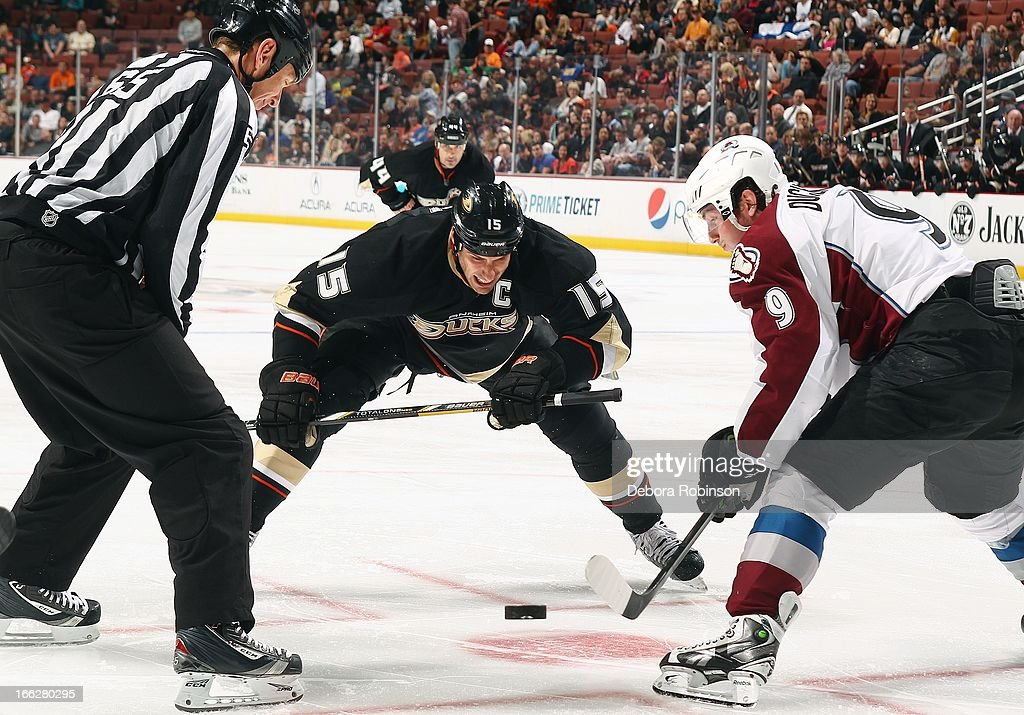 Linesman Pierre Racicot #65 drops the puck for a faceoff between Ryan Getzlaf #15 of the Anaheim Ducks and Matt Duchene #9 of the Colorado Avalanche April 10, 2013 at Honda Center in Anaheim, California.