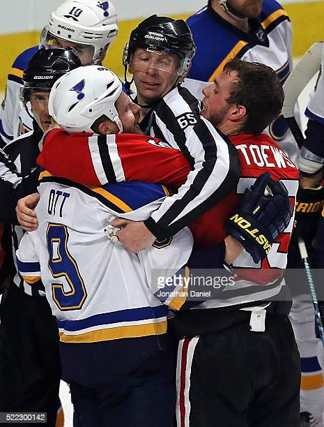 Linesman Pierre Racicot gets between Steve Ott of the St Louis Blues and Jonathan Toews of the Chicago Blackhawks in Game Three of the Western...