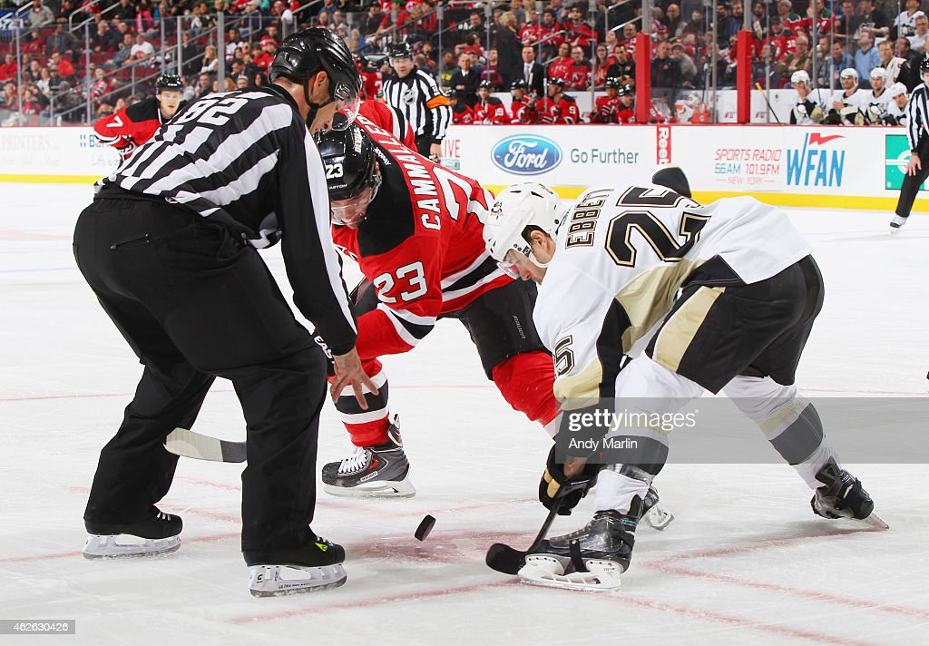 Linesman Ryan Galloway drops the puck on a faceoff between Andrew Ebbett of the Pittsburgh Penguins and Mike Cammalleri of the New Jersey Devils...