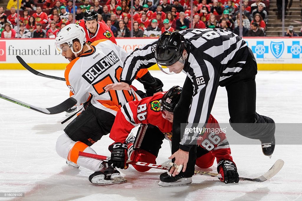Linesman Ryan Galloway #82 falls over Teuvo Teravainen #86 of the Chicago Blackhawks and Pierre-Edouard Bellemare #78 of the Philadelphia Flyers in the first period of the NHL game at the United Center on March 16, 2016 in Chicago, Illinois.