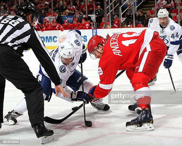 Linesman Scott Driscoll drops the puck between Tyler Johnson of the Tampa Bay Lightning and Joakim Andersson of the Detroit Red Wings during an NHL...