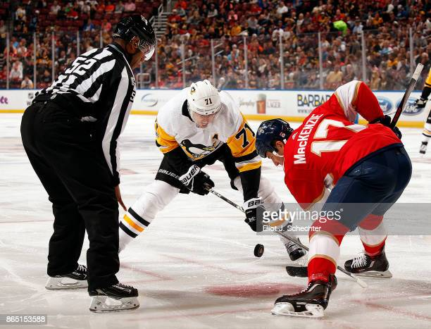 Linesman Shandor Alphonso drops the puck for a face off between Evgeni Malkin of the Pittsburgh Penguins and Derek MacKenzie of the Florida Panthers...
